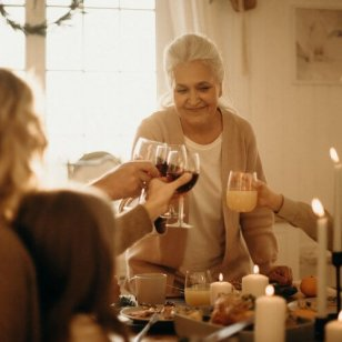 woman-on-gray-cardigan-standing-near-table-doing-cheers-3171199